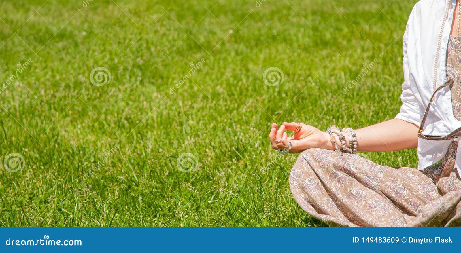Η γυναίκα η συνεδρίαση στο Lotus θέτει στη χλόη στο πάρκο Ύφος Boho με τα εξαρτήματα, τα δαχτυλίδια και τα βραχιόλια