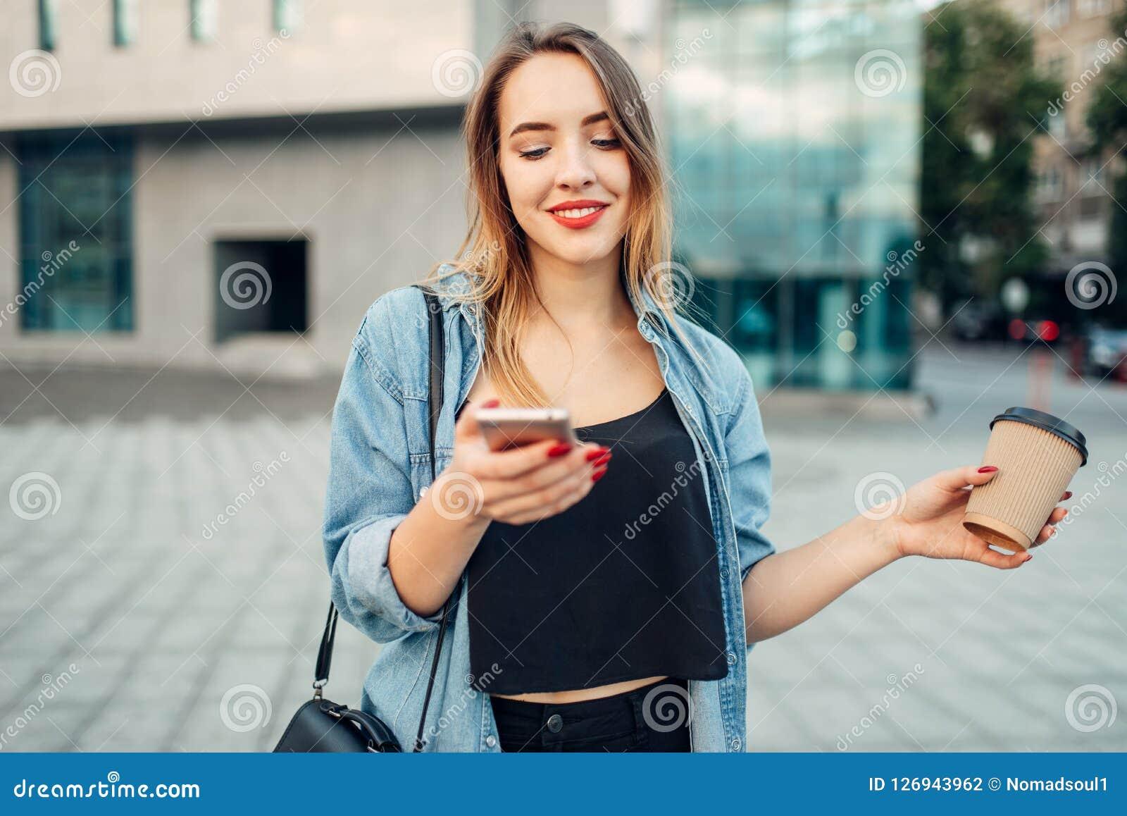 Η γυναίκα τηλεφωνικών εξαρτημένων κρατά τη συσκευή και τον καφέ διαθέσιμους