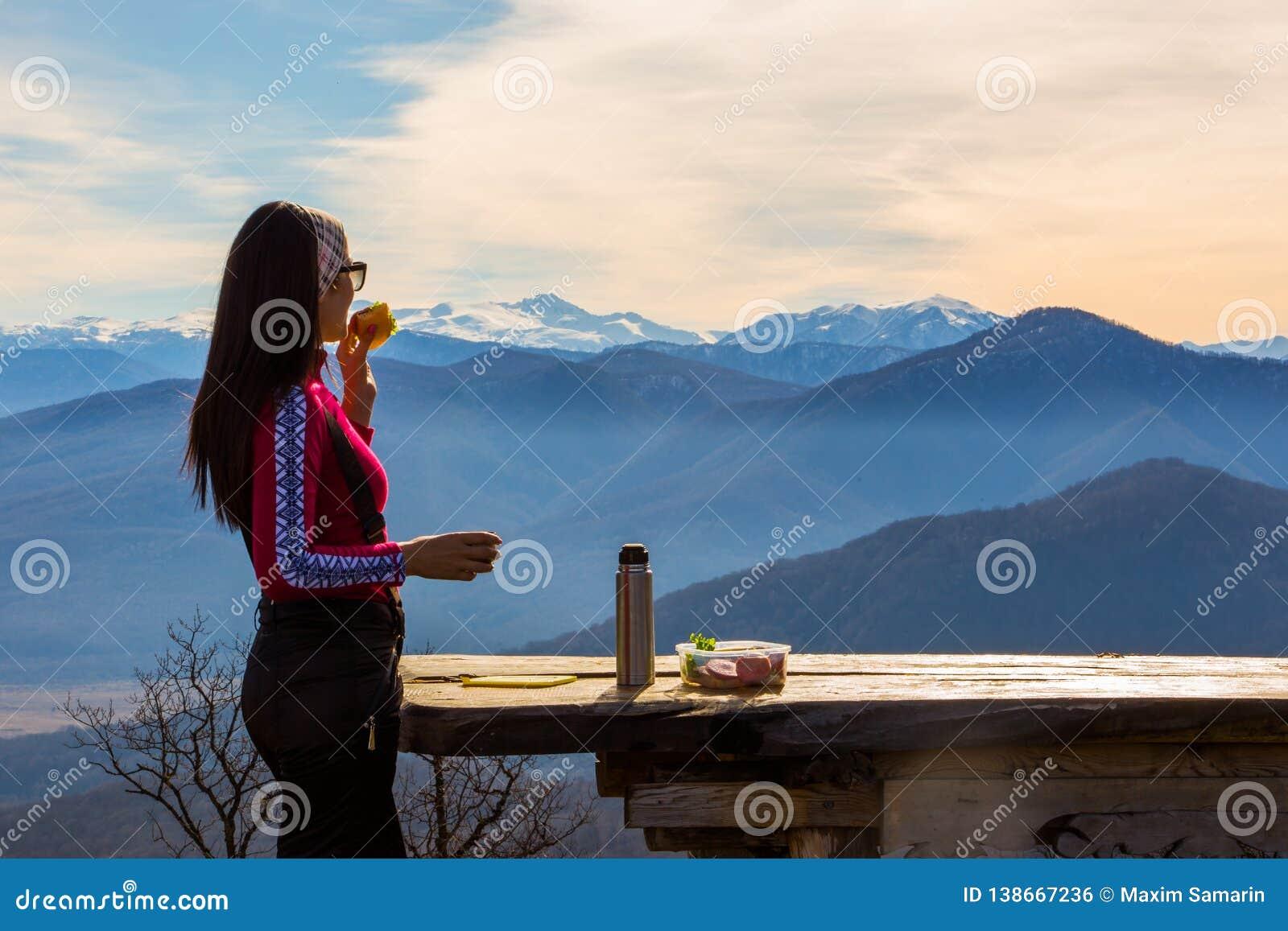 Η γυναίκα τρώει τα σάντουιτς και πίνει το τσάι ενάντια στο τοπίο με τα βουνά