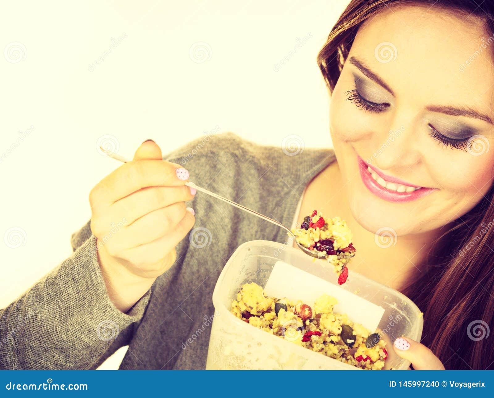 Η γυναίκα τρώει oatmeal με τα ξηρά φρούτα dieting