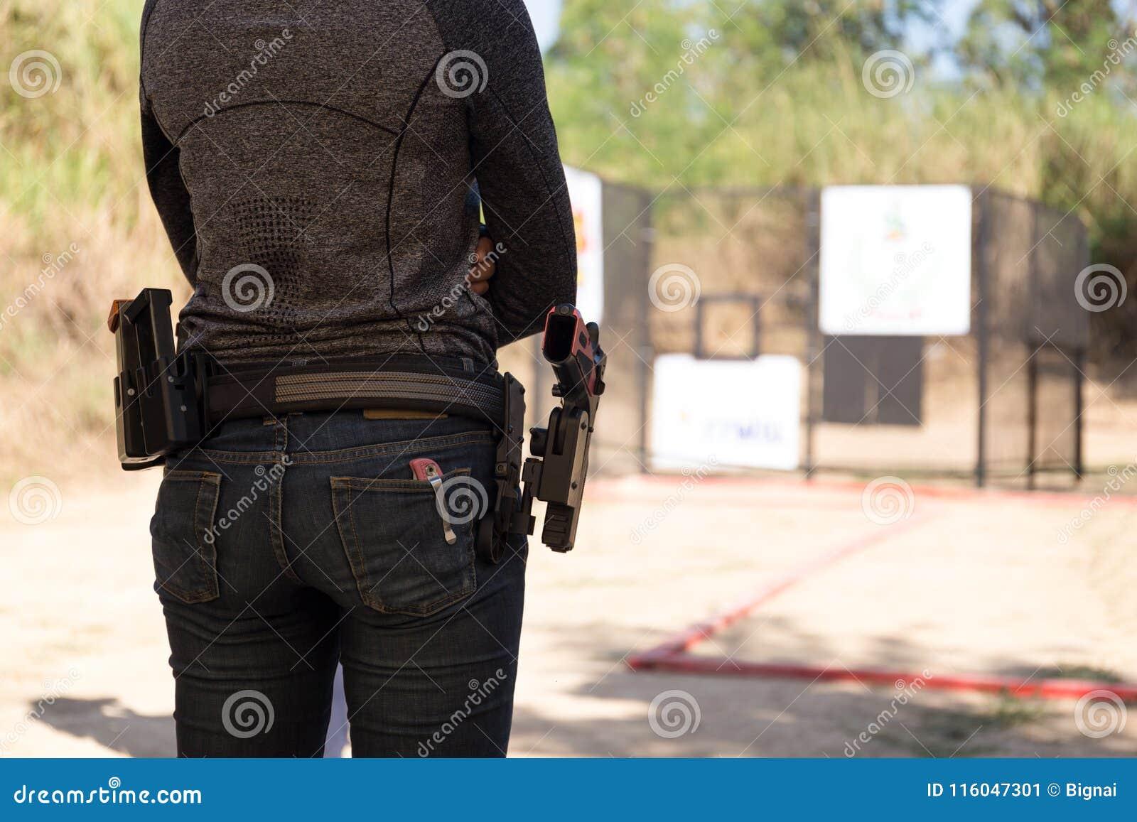 Η γυναίκα φέρνει το πυροβόλο όπλο στη ζώνη του
