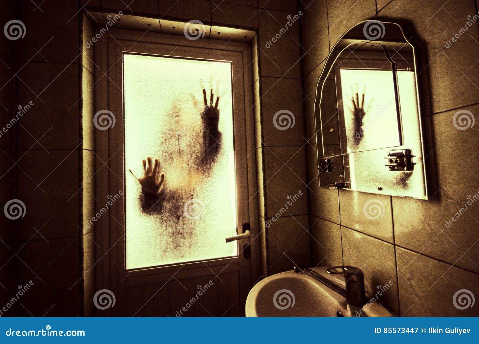 Η γυναίκα φρίκης παραθύρων στην ξύλινη χεριών λαβής έννοια αποκριών σκηνής κλουβιών τρομακτική θόλωσε τη σκιαγραφία της μάγισσας