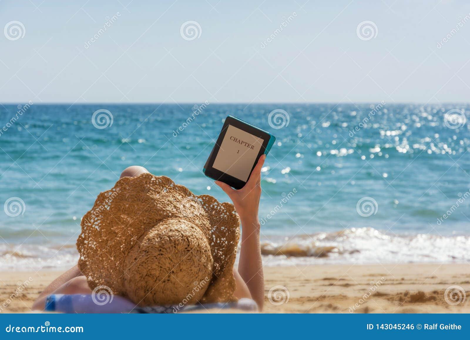 Η γυναίκα χαλαρώνει διαβάζοντας στην παραλία