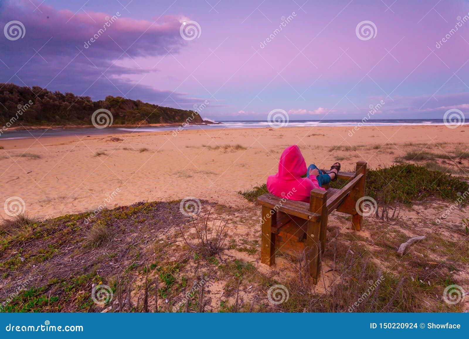 Η γυναίκα χαλαρώνει στον πάγκο αγνοώντας την παραλία στο σούρουπο απογεύματος