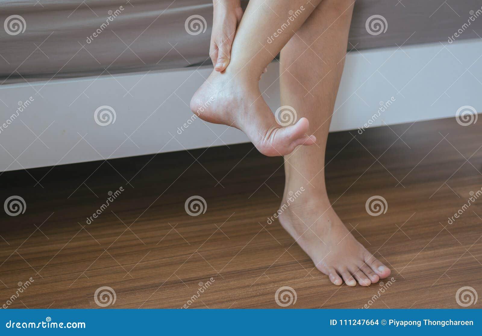 Η γυναίκα χεριών με το τραυματισμό αστραγάλου, πόνος μασάζ, θηλυκό που βλάπτει και που κρατά επίπονος ο αστράγαλος