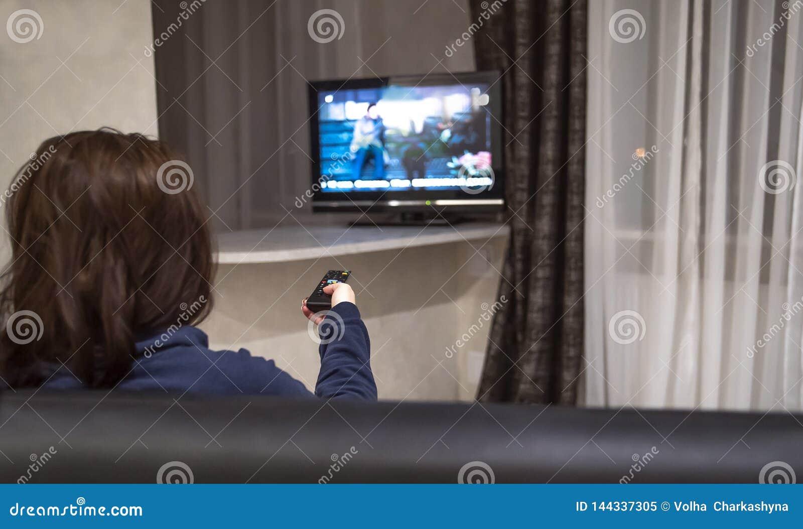 Η γυναίκα Brunette αλλάζει τα τηλεοπτικά κανάλια καθμένος στο σπίτι στον καναπέ, οπισθοσκόπο