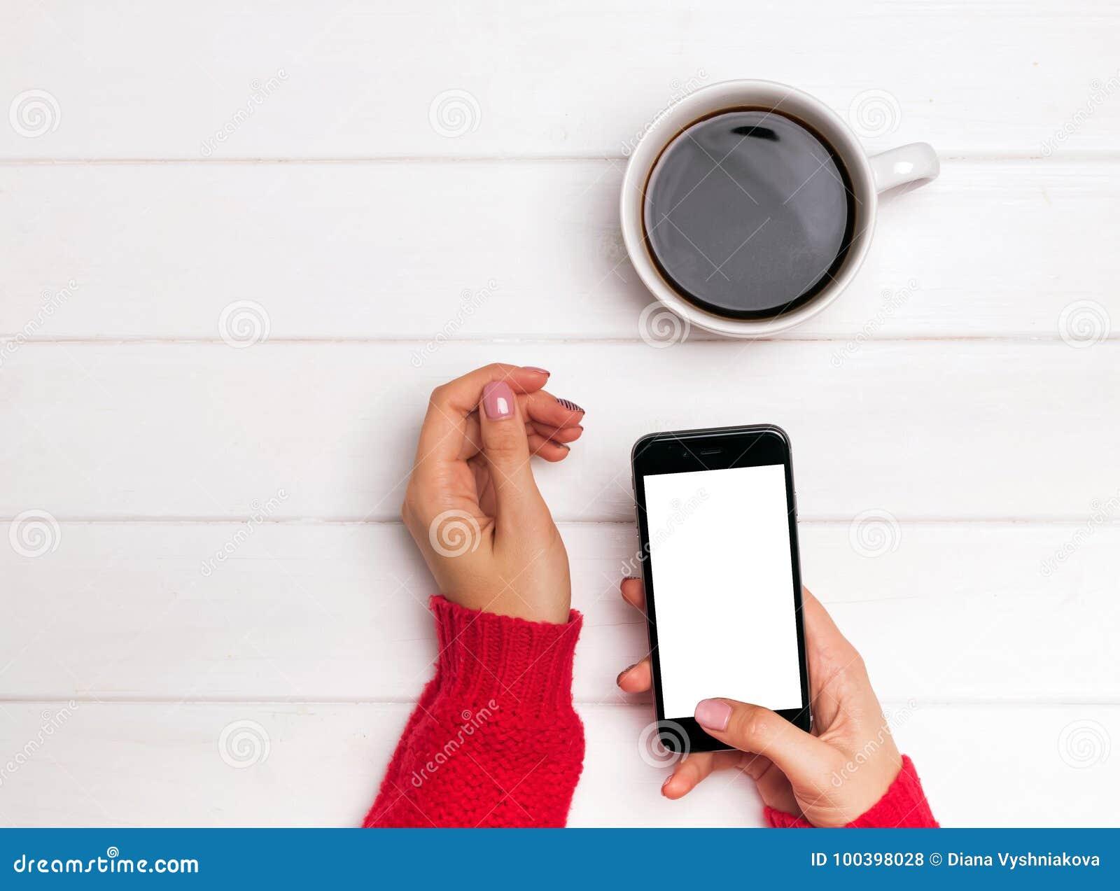 Η γυναίκα ` s παραδίδει το κόκκινο smartphone εκμετάλλευσης πουλόβερ με το κενό λευκό