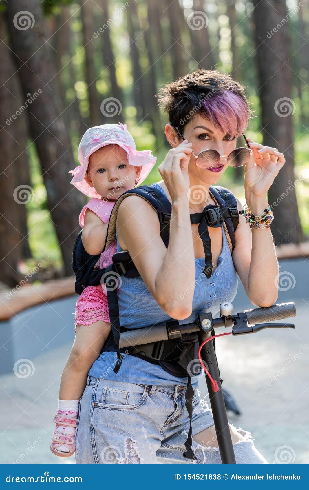 Η δροσερή ελκυστική γυναίκα απολαμβάνει ένα ηλεκτρικό μηχανικό δίκυκλο με την κόρη της στη σφεντόνα