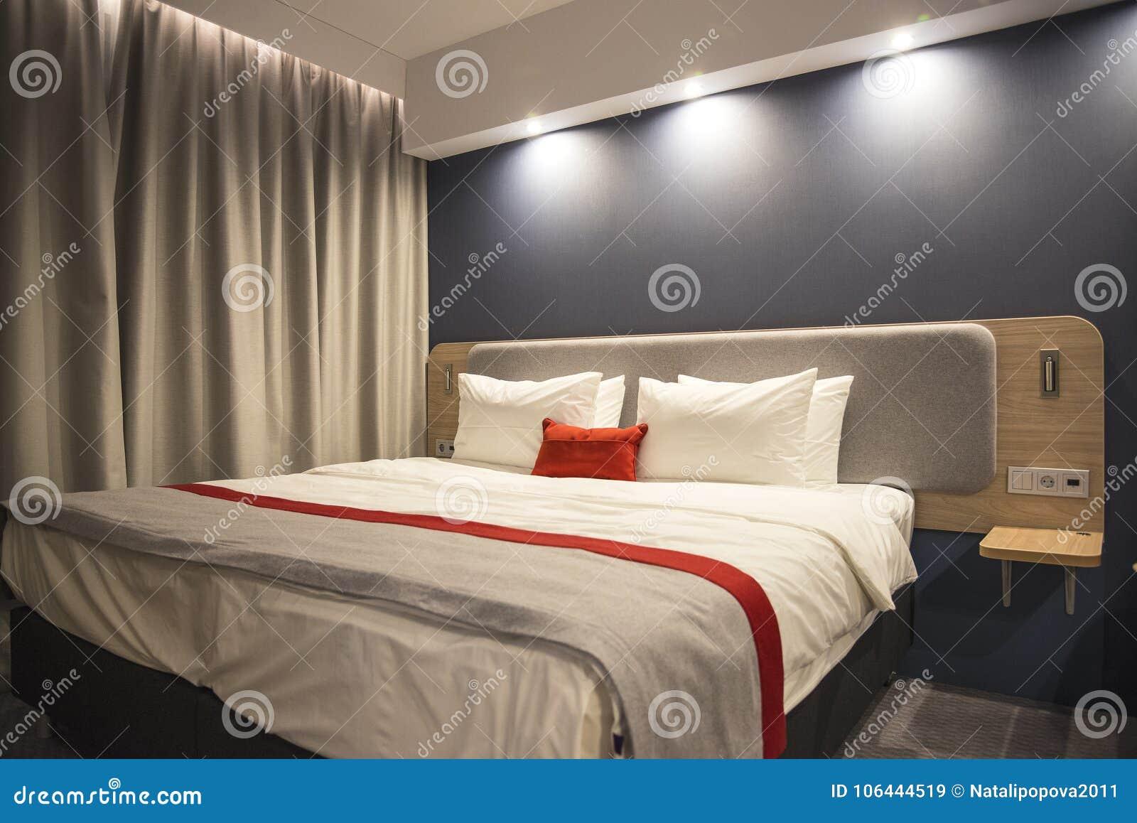 Η εικόνα ενός εσωτερικού κρεβατοκάμαρων Ένα μεγάλο κρεβάτι με τέσσερα μαξιλάρια