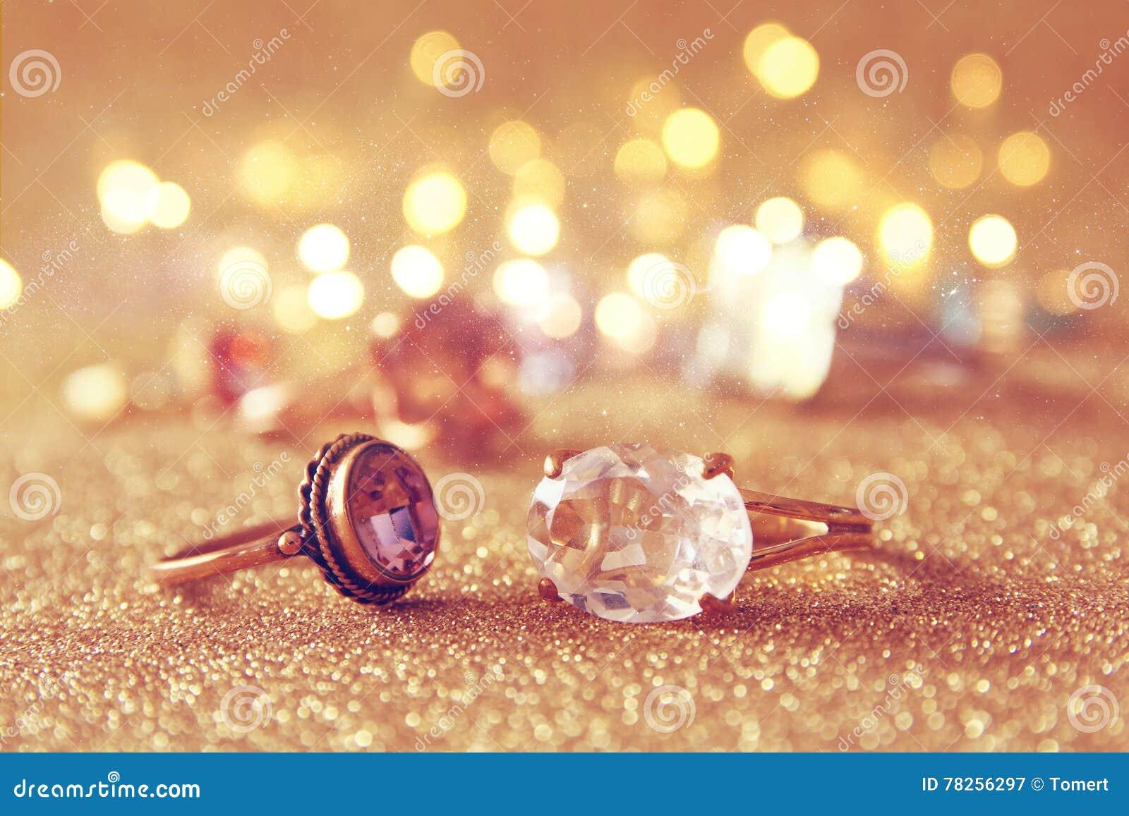Η εικόνα των κομψών χρυσών δαχτυλιδιών στο χρυσό ακτινοβολεί υπόβαθρο