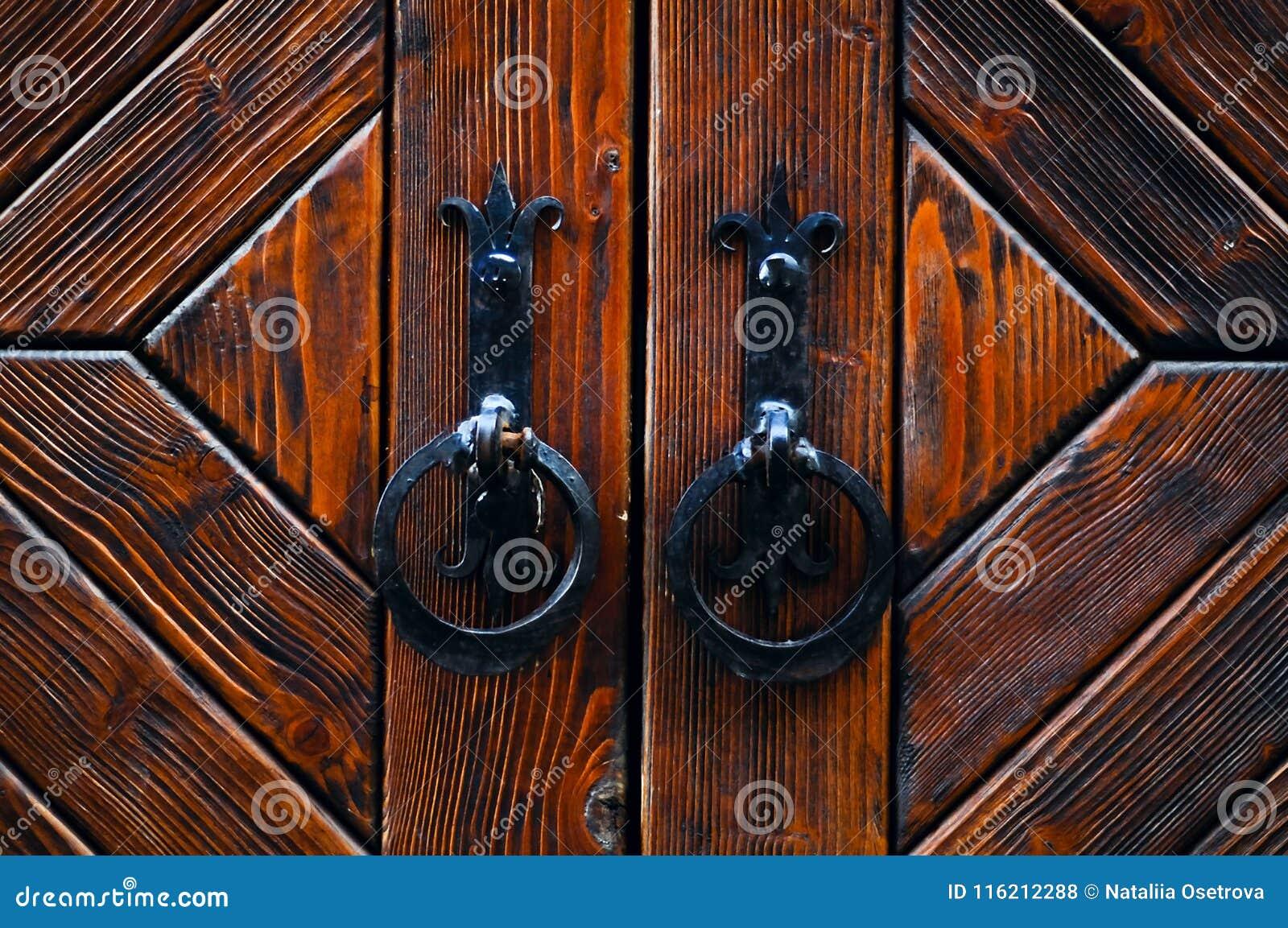 Η εκλεκτής ποιότητας μεταλλική πόρτα χειρίζεται το Μαύρο σε ένα ξύλινο υπόβαθρο, έννοια των αυθεντικών αντικειμένων, διάστημα αντ