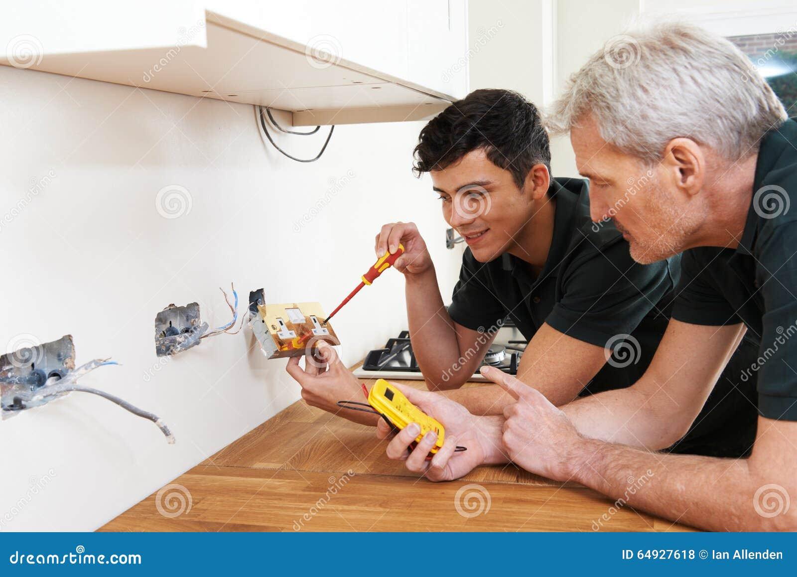 Ηλεκτρολόγος με την εργασία μαθητευόμενων στο νέο σπίτι