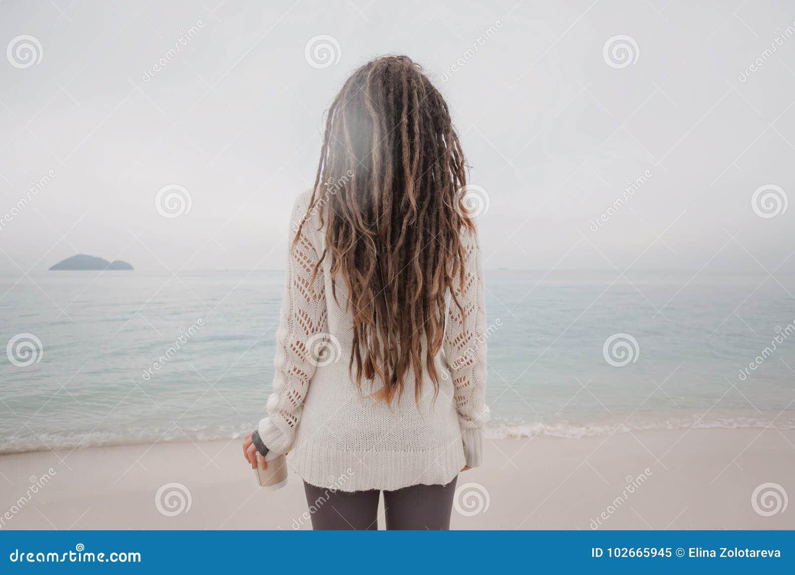 Η ελκυστική νέα γυναίκα στο πουλόβερ προσέχει τη γραμμή οριζόντων