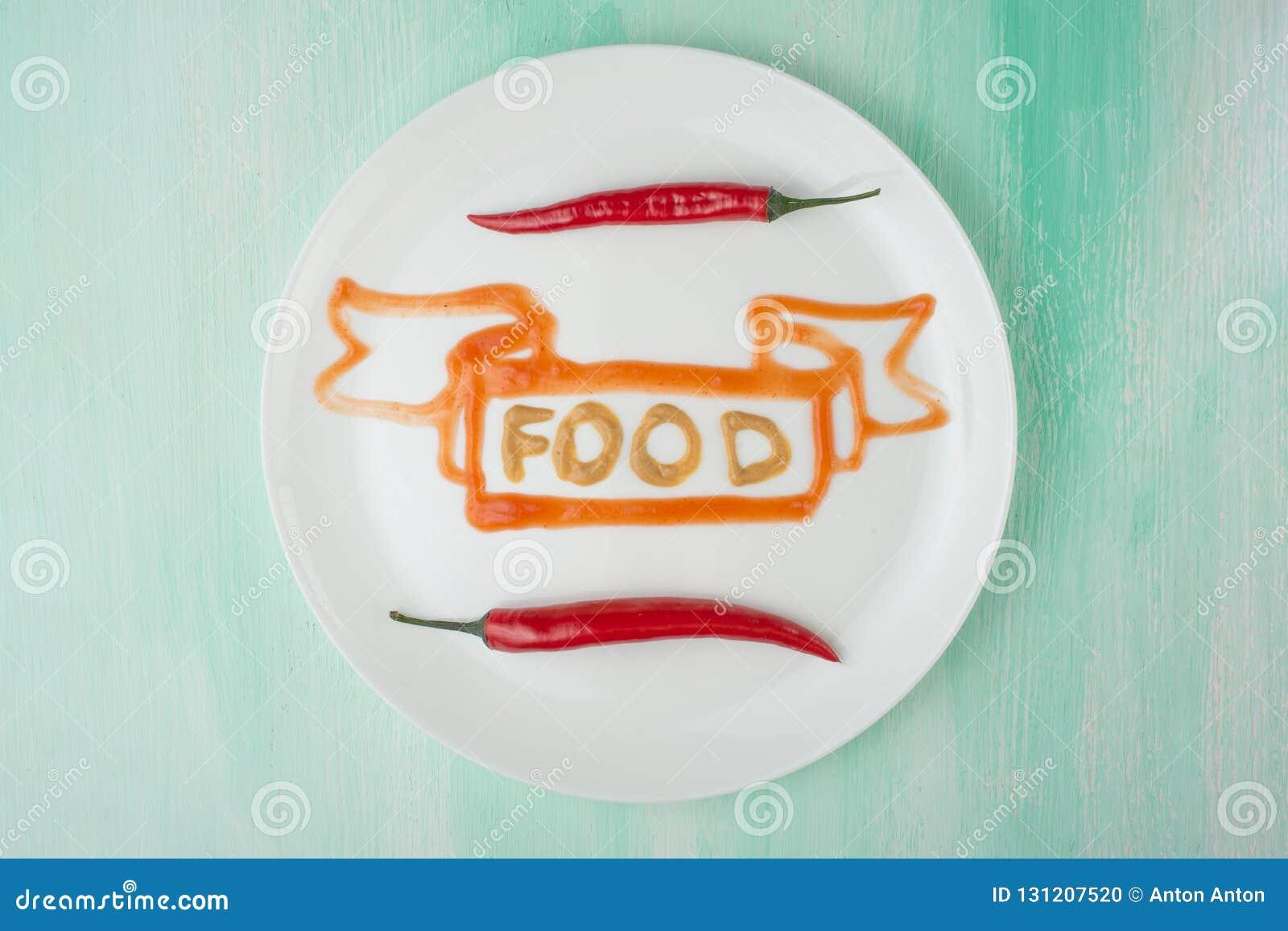 Η επιγραφή είναι ένα γεύμα της μουστάρδας και κόκκινο πιπέρι, ένας δημιουργικός των τροφίμων σε ένα άσπρο πιάτο Η έννοια των τροφ
