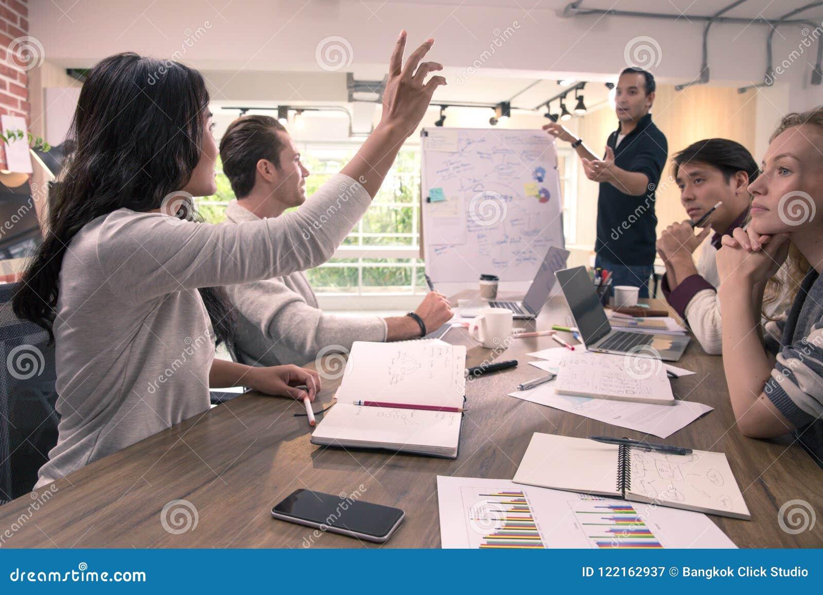 Η επιχειρησιακή γυναίκα αυξάνει το χέρι για υποβάλλει την ερώτηση στον επιχειρηματία που στέκεται και εξηγεί το διάγραμμα μπροστά