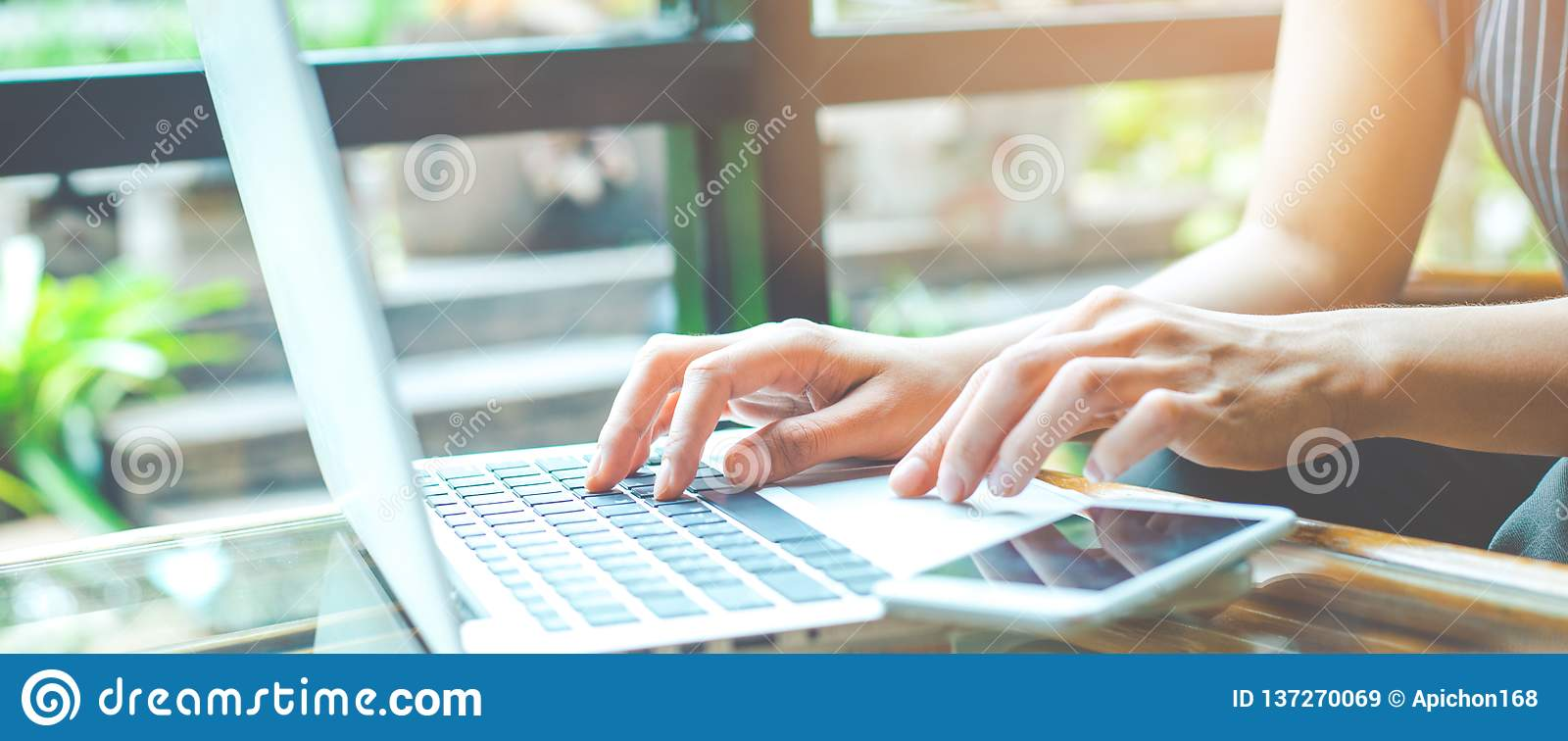 Η επιχειρησιακή γυναίκα που λειτουργούν με έναν φορητό προσωπικό υπολογιστή και οι χρήσεις ένα κύτταρο τηλεφωνούν στο γραφείο