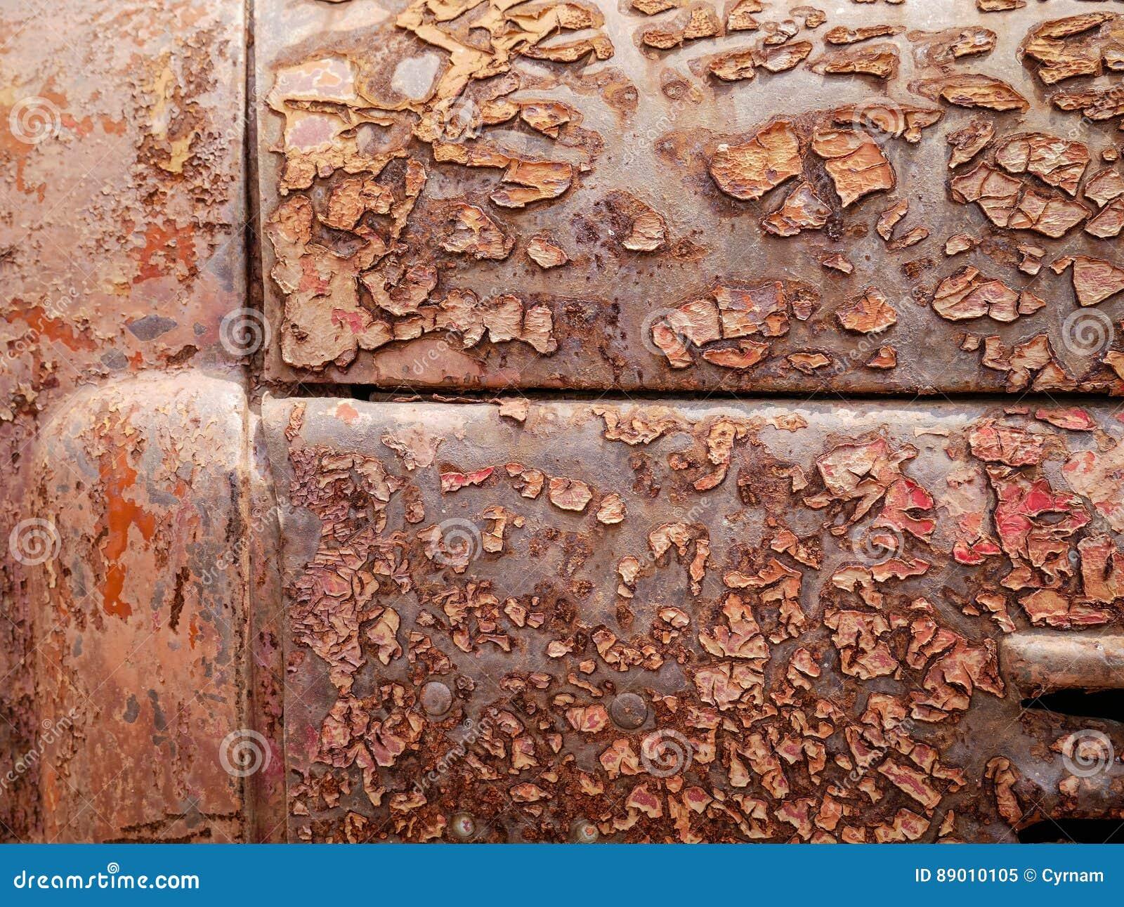 Η λεπτομέρεια και κλείνει επάνω της σκουριάς στο μέταλλο αυτοκινήτων με το ράγισμα, την παρουσία σκουριάς και τη διάβρωση, όμορφο