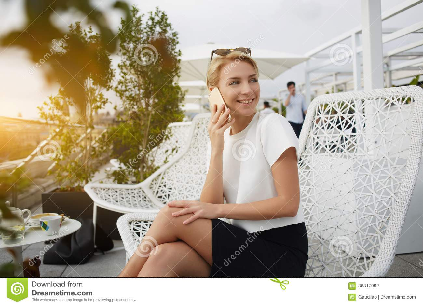 Η ευτυχής γυναίκα χαμογελά τον εχθρό κάποιος, ενώ μιλά στο τηλέφωνο κυττάρων κατά τη διάρκεια του υπολοίπου στον καφέ