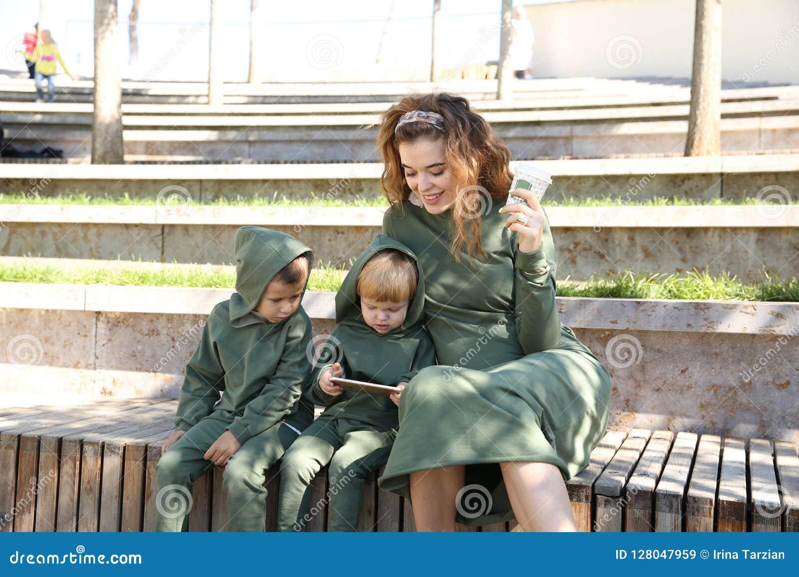 Η ευτυχής μητέρα με τα παιδιά στη μοντέρνη οικογένεια ενδυμάτων κοιτάζει σε ένα πάρκο