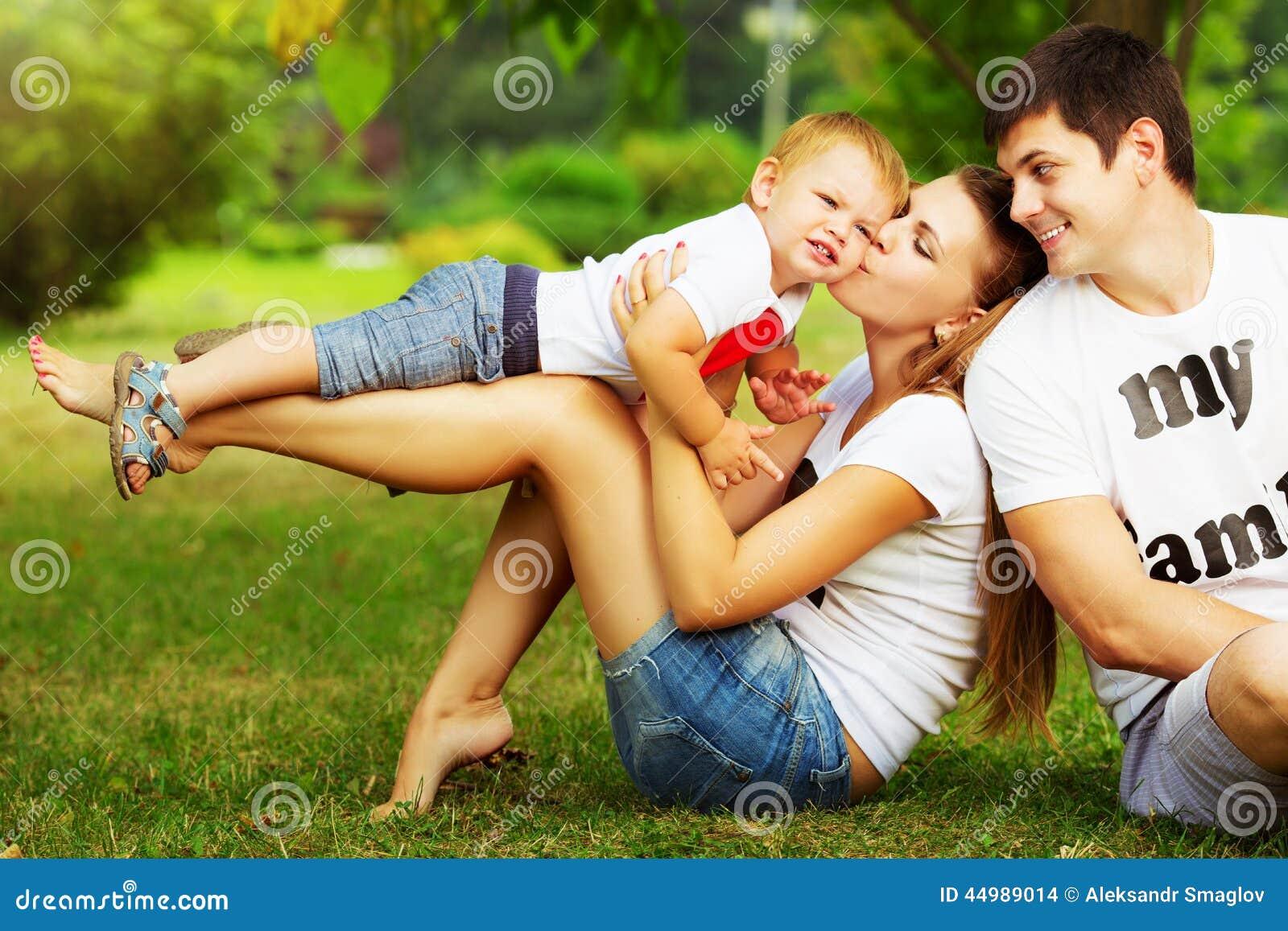Η ευτυχής νέα οικογένεια έχει τη διασκέδαση στο πράσινο outdoo θερινών πάρκων