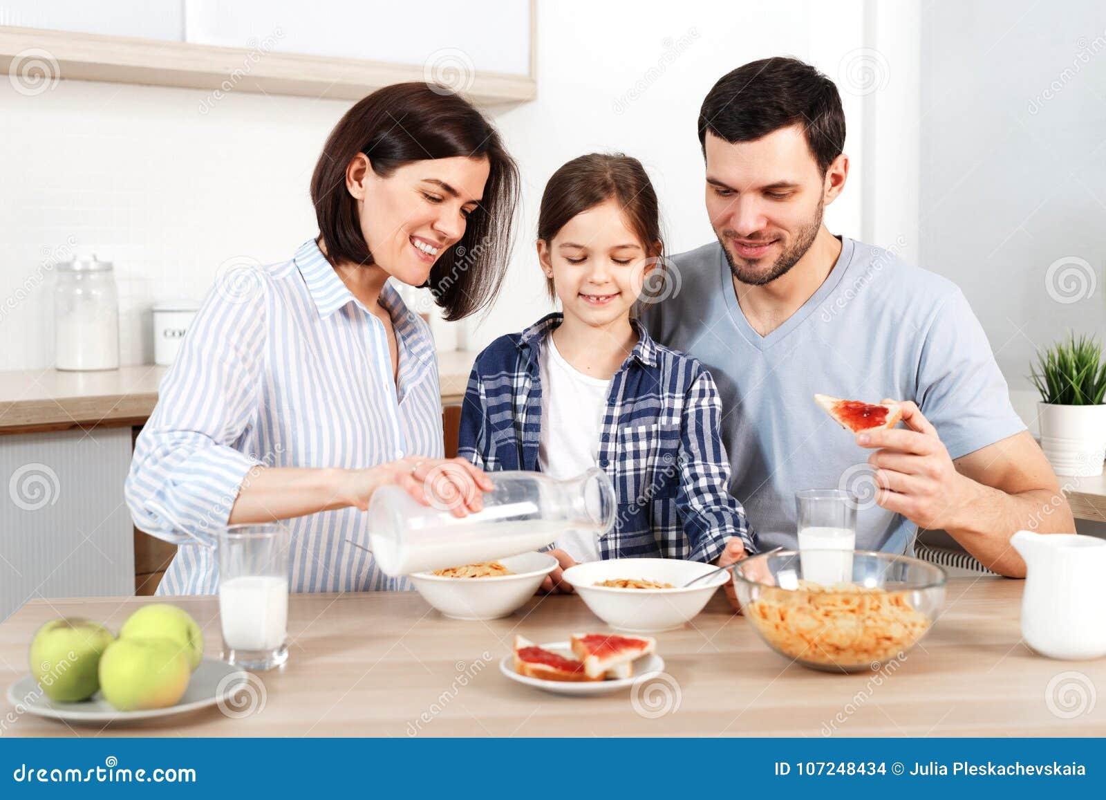 Η ευτυχής οικογένεια έχει το υγιές πρόγευμα από κοινού Η χαμογελώντας μητέρα χύνει το γάλα στο κύπελλο με τα δημητριακά, τρώει τα