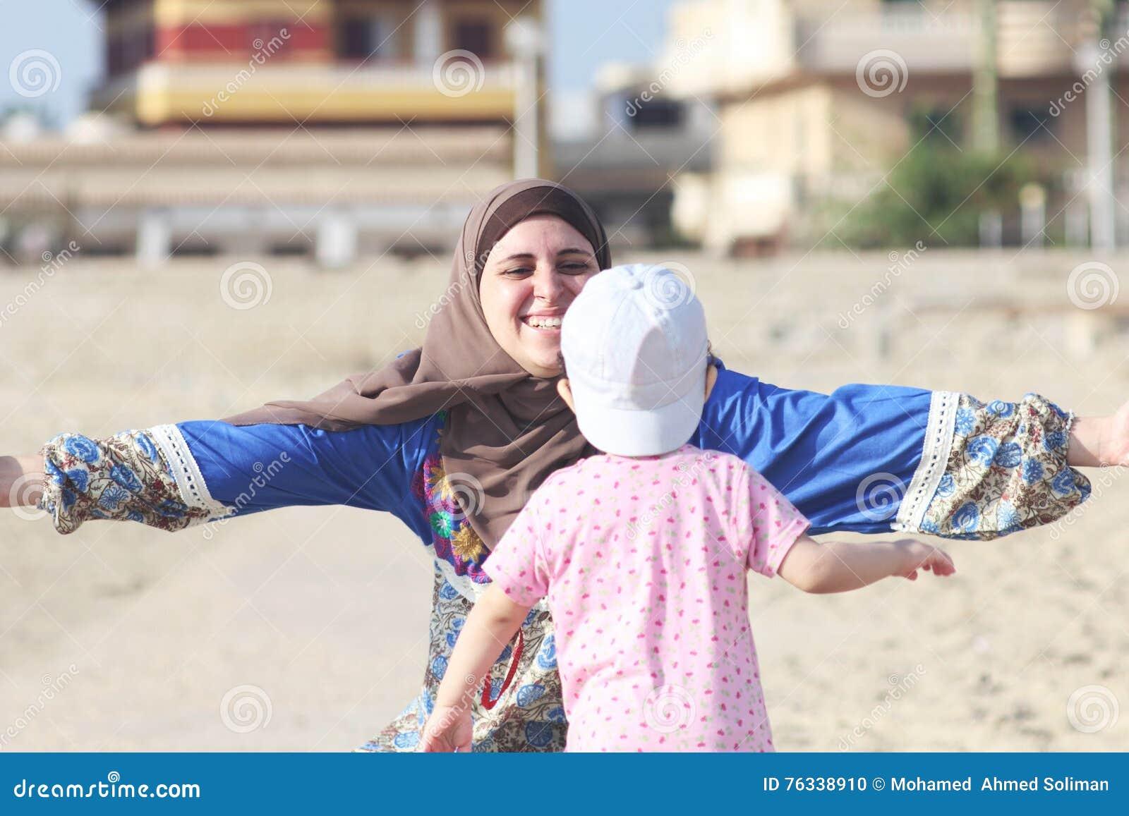 Η ευτυχής χαμογελώντας αραβική μουσουλμανική μητέρα αγκαλιάζει το κοριτσάκι της