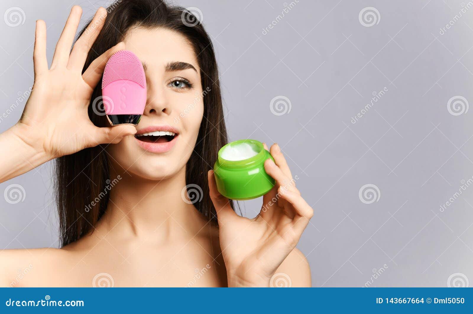 Η ευτυχής όμορφη γυναίκα καλύπτει το μάτι της με τη ρόδινη καθαρίζοντας συσκευή σιλικόνης βουρτσών προσώπου για το δέρμα και παρο