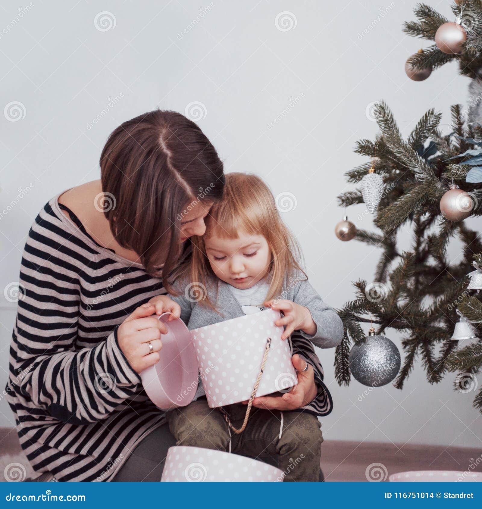 Η ευτυχή οικογενειακά μητέρα και το μωρό διακοσμούν το χριστουγεννιάτικο δέντρο