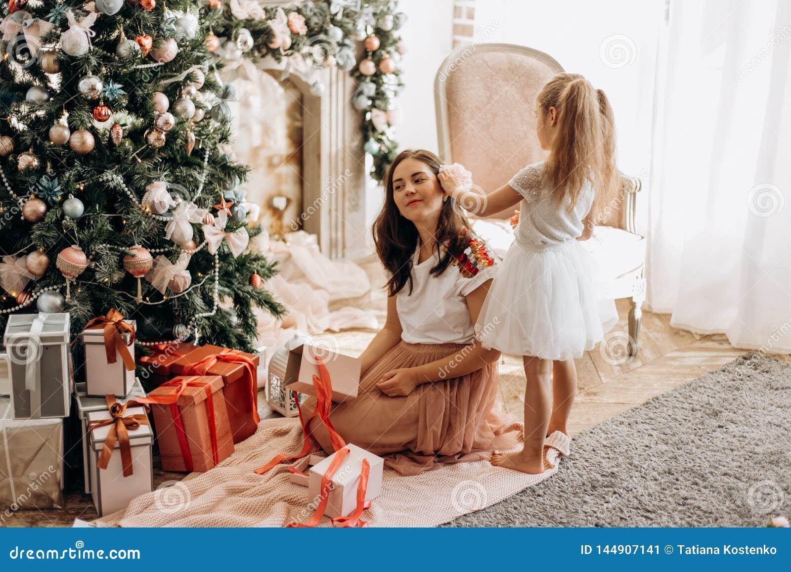 Η ευτυχείς νέες μητέρα και λίγη κόρη στο συμπαθητικό φόρεμα κάθονται τ