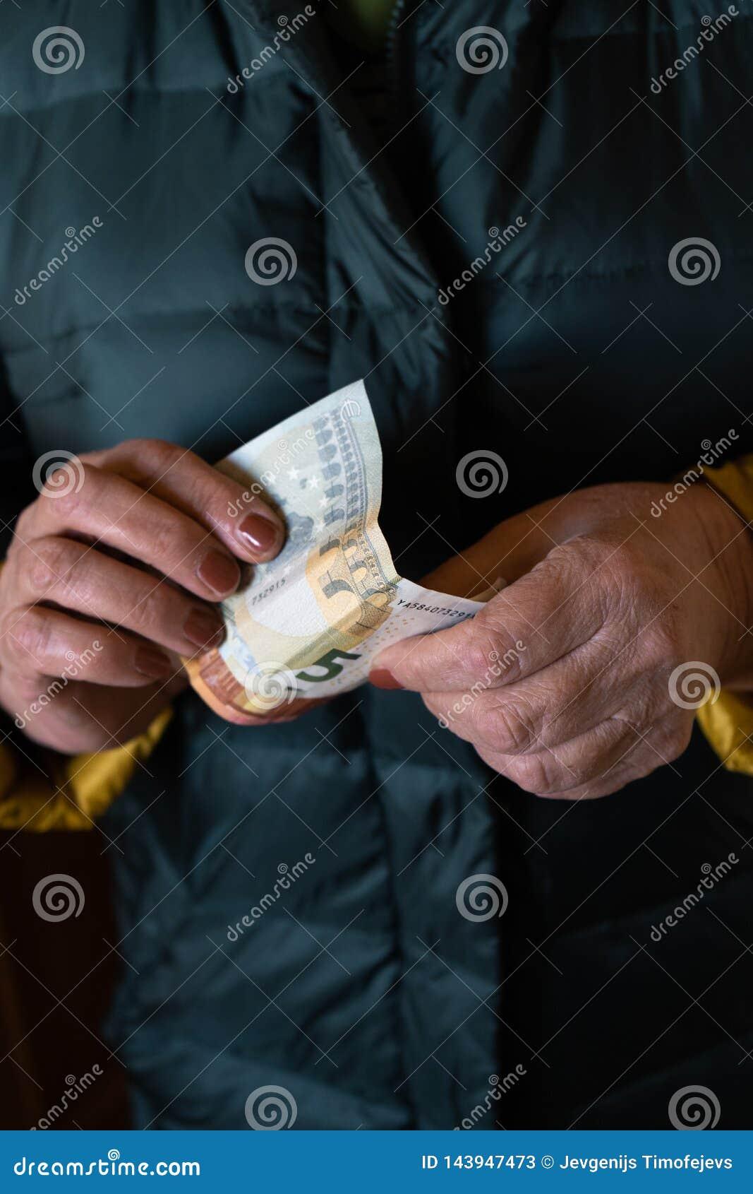 Η ηλικιωμένη ανώτερη γυναίκα κρατά τα ΕΥΡΟ- τραπεζογραμμάτια - ανατολικο-ευρωπαϊκή σύνταξη μισθών