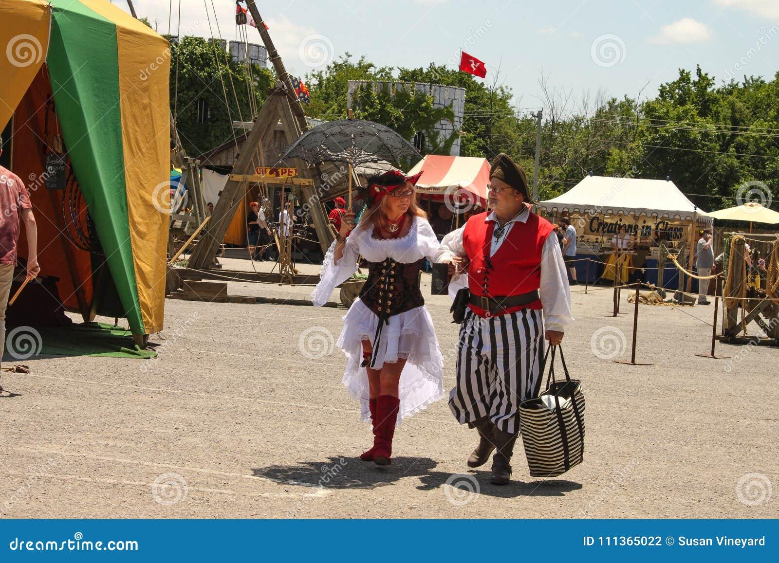 Η ηλικιωμένη γυναίκα έντυσε στο πολύ προκλητικό κοστούμι και ο ηληκιωμένος έντυσε ως πειρατής εξετάζει ο ένας τον άλλον στοργικά