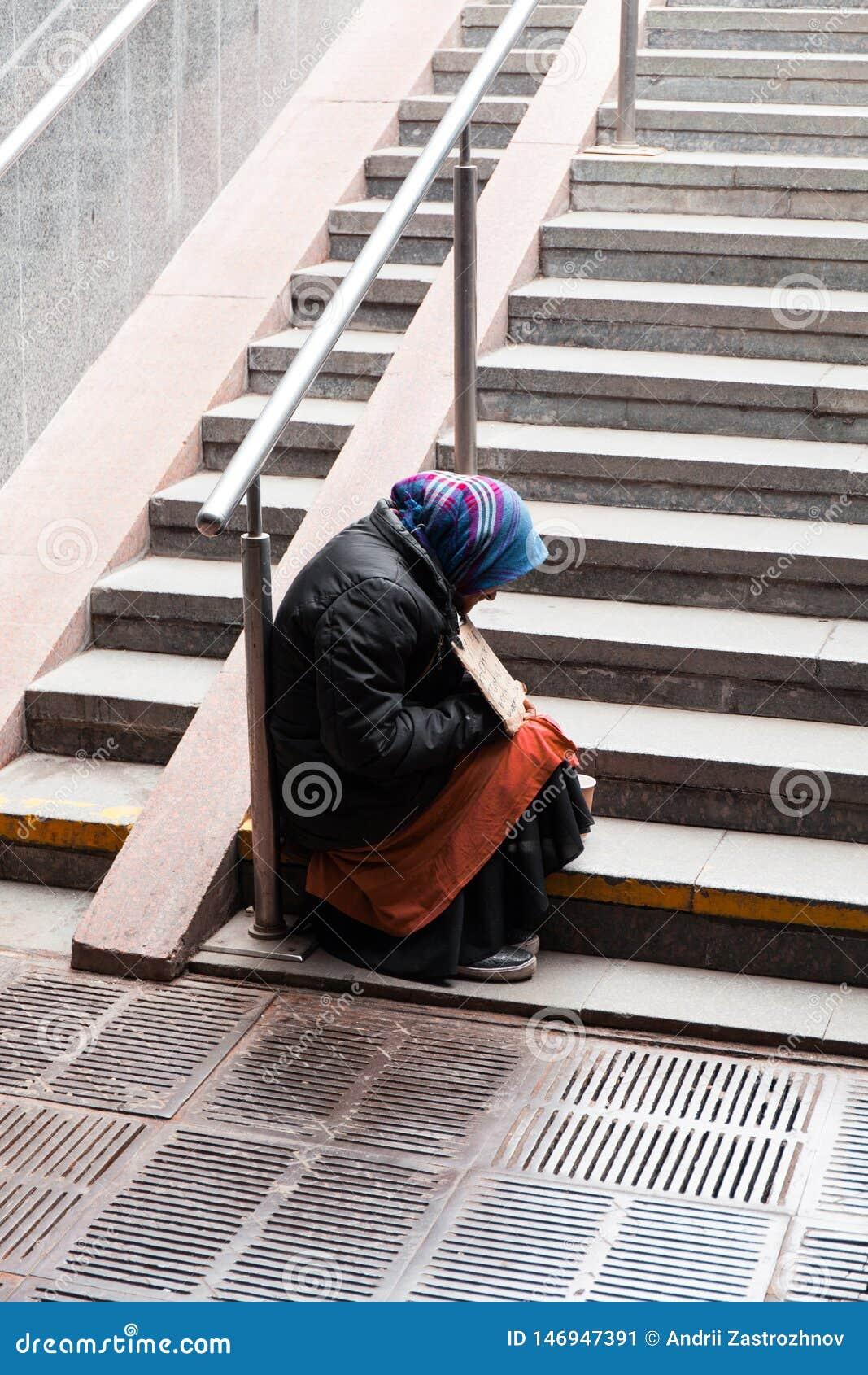 Η ηλικιωμένη γυναίκα επαιτών κάθεται στα σκαλοπάτια