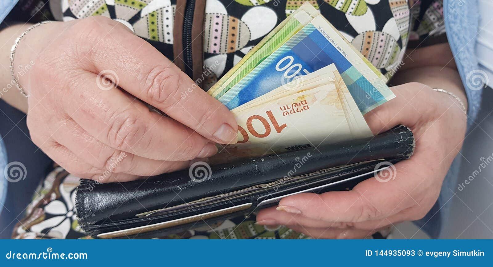 Η ηλικιωμένη γυναίκα κρατά στα χέρια τα ισραηλινά χρήματα μετρητών