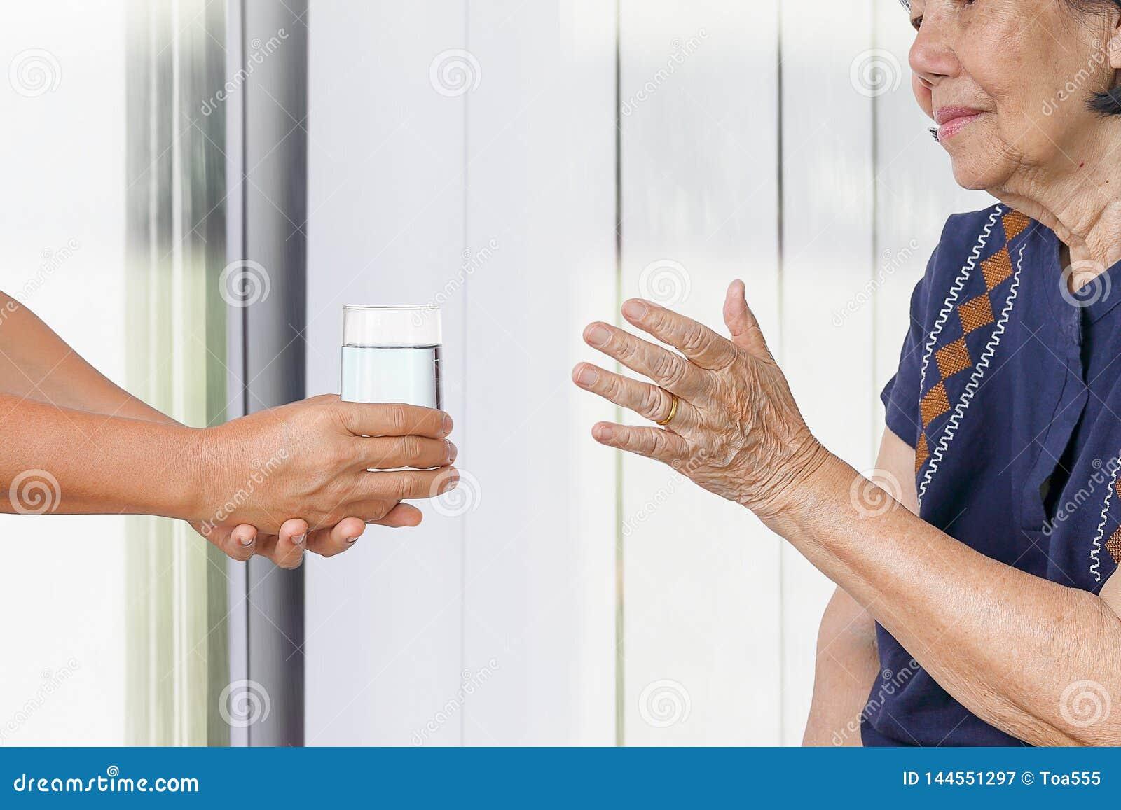 Η ηλικιωμένη γυναίκα παίρνει ένα ποτήρι του νερού από το caregiver