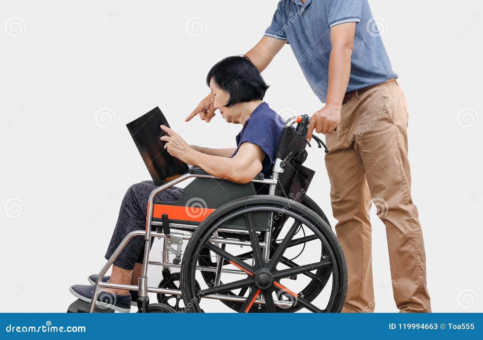 Η ηλικιωμένη γυναίκα που διαβάζει ένα βιβλίο στην αναπηρική καρέκλα με το γιο παίρνει την προσοχή