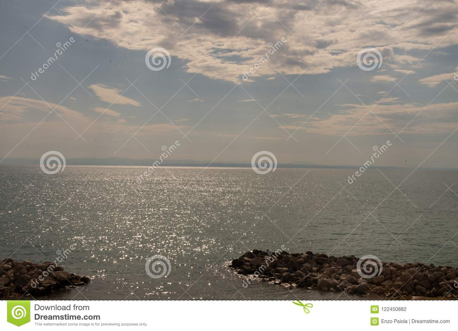 Η θάλασσα Bibione, Βένετο, Ιταλία, με μια εκθαμβωτική αντανάκλαση και τα σύννεφα στον ουρανό που καλύπτει τις ακτίνες ήλιων ` s