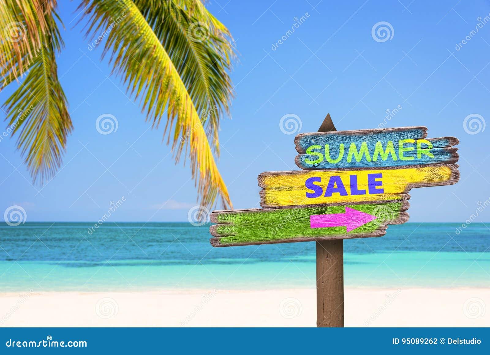Η θερινή πώληση που γράφτηκε στην κρητιδογραφία χρωμάτισε τα ξύλινα σημάδια κατεύθυνσης, την παραλία και το υπόβαθρο φοινίκων
