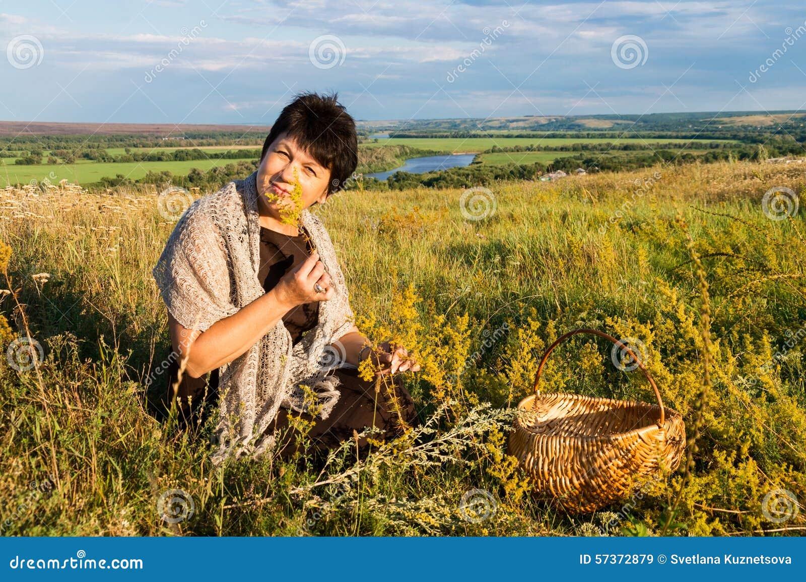 Η θετική γυναίκα πενηντάχρονων συλλέγει τη χλόη στο λιβάδι ενάντια