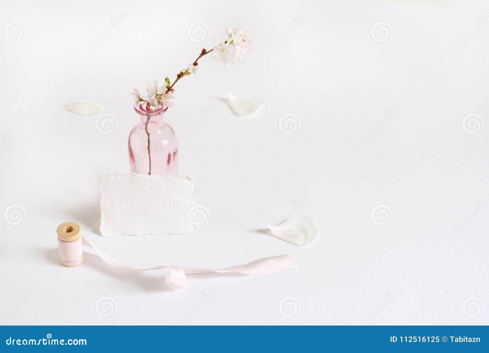 Η θηλυκή σκηνή προτύπων χαρτικών άνοιξη με μια χειροποίητη ευχετήρια κάρτα εγγράφου, το στροφίο της κορδέλλας μεταξιού και το κερ