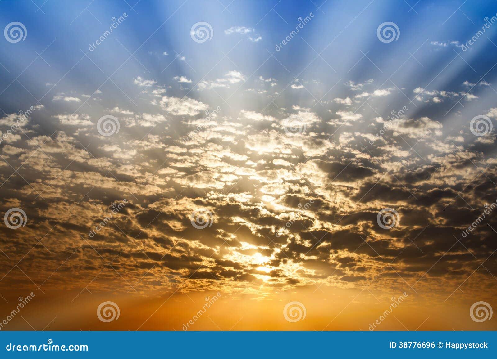 Ηλιαχτίδα μέσω του μπλε και πορτοκαλιού ουρανού σύννεφων