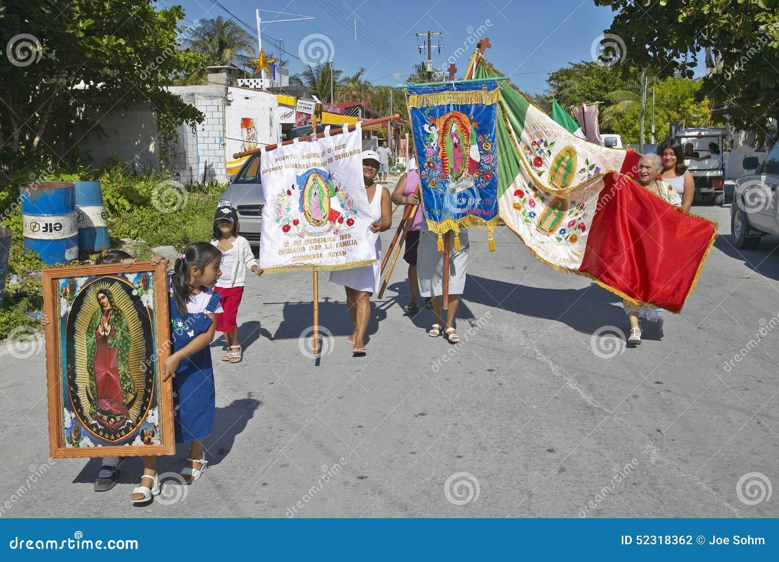 Ηλικιωμένες γυναίκες και παιδιά που βαδίζουν μέσω των οδών Puerto Morelos που φέρνουν τη μεξικάνικα σημαία και Virgen de Guadalup