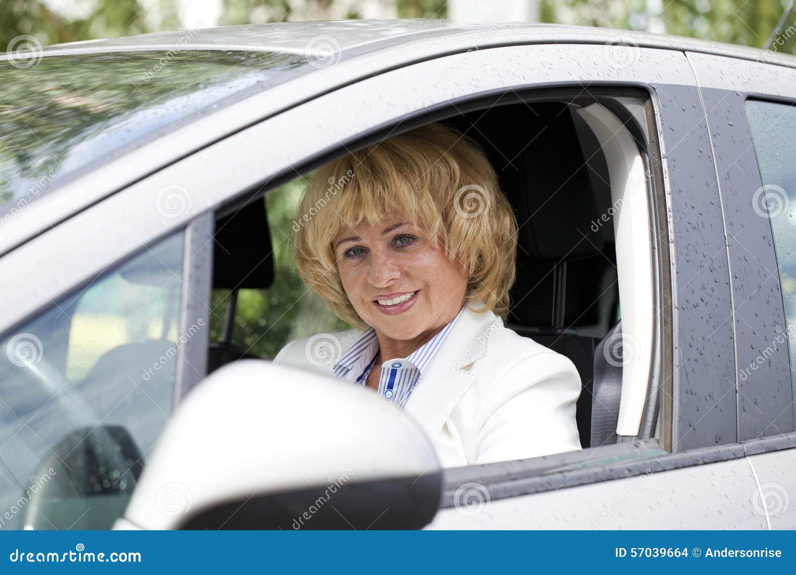 Ηλικιωμένη ευτυχής ηλικιωμένη γυναίκα οδηγών 55-60 έτη στο σακάκι που το εναλλασσόμενο ρεύμα