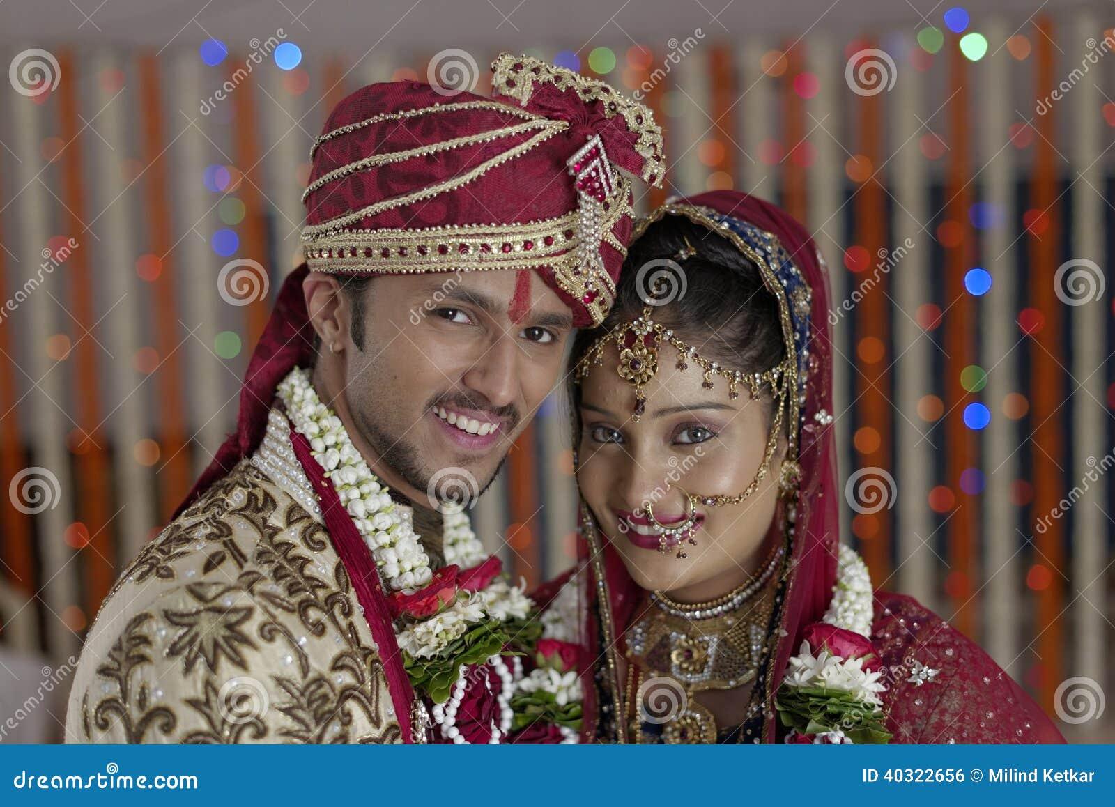 Η ινδική ινδή νύφη & καλλωπίζει ένα ευτυχές χαμογελώντας ζεύγος.