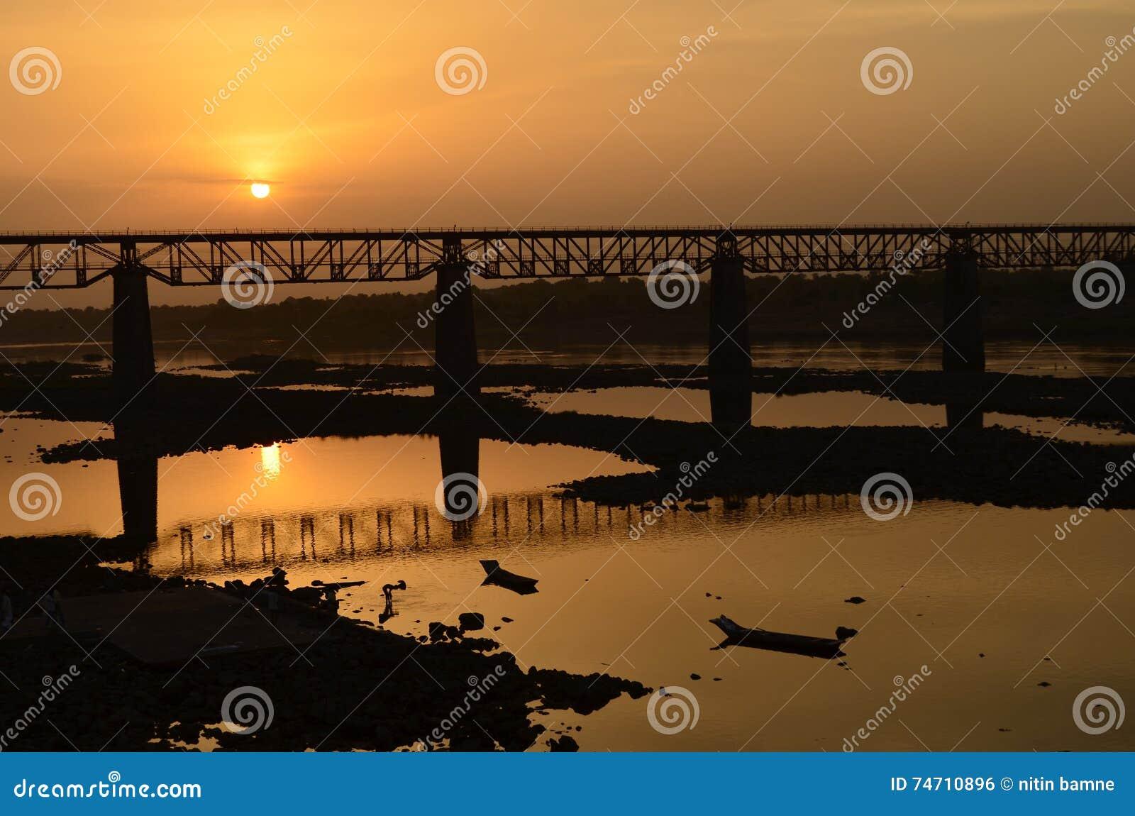 Ηλιοβασίλεμα με μια γέφυρα τραίνων στον ποταμό narmada indore πλησίον, Ινδία-2015