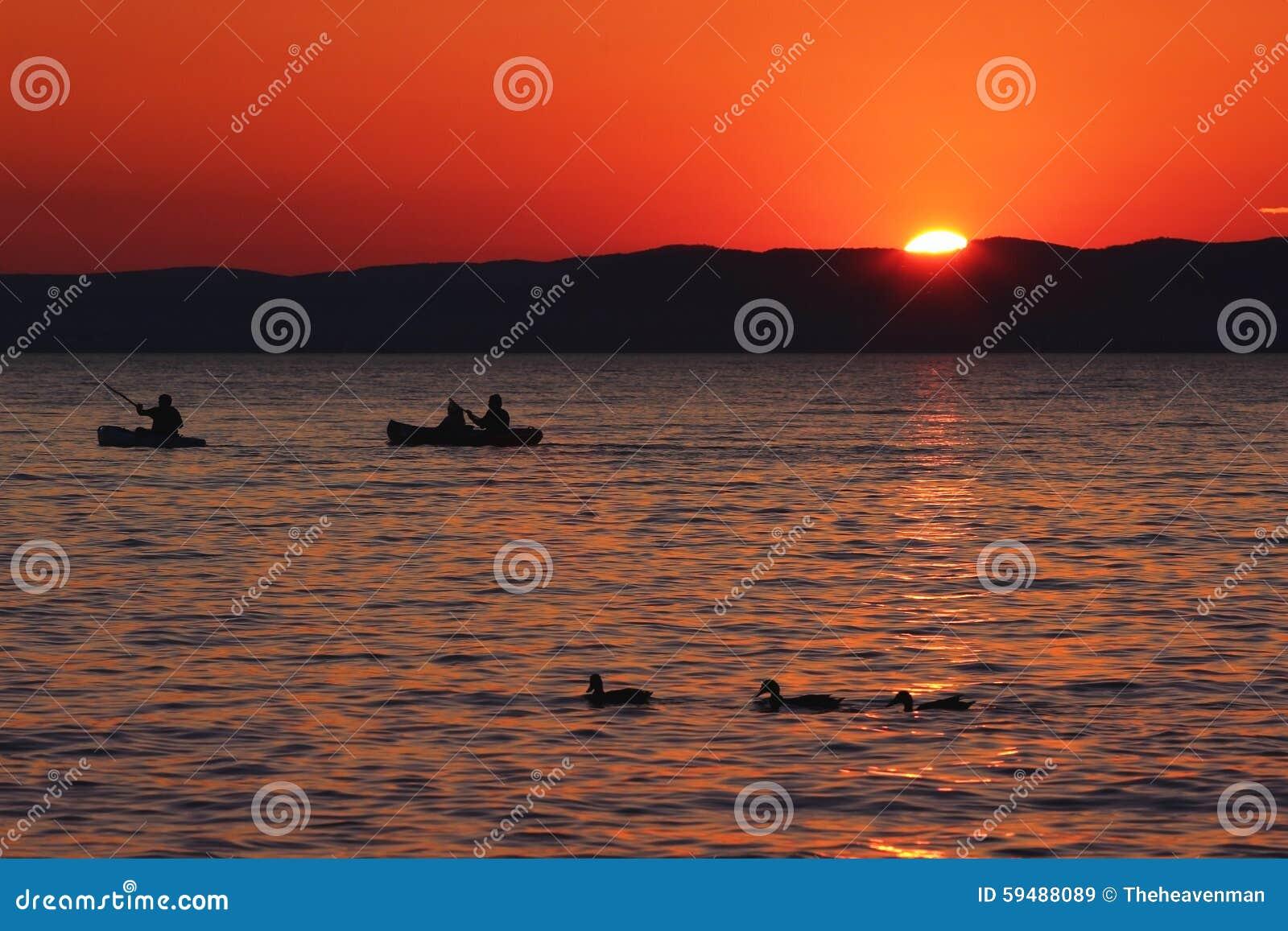 Ηλιοβασίλεμα πέρα από τη λίμνη με τις βάρκες και τις πάπιες
