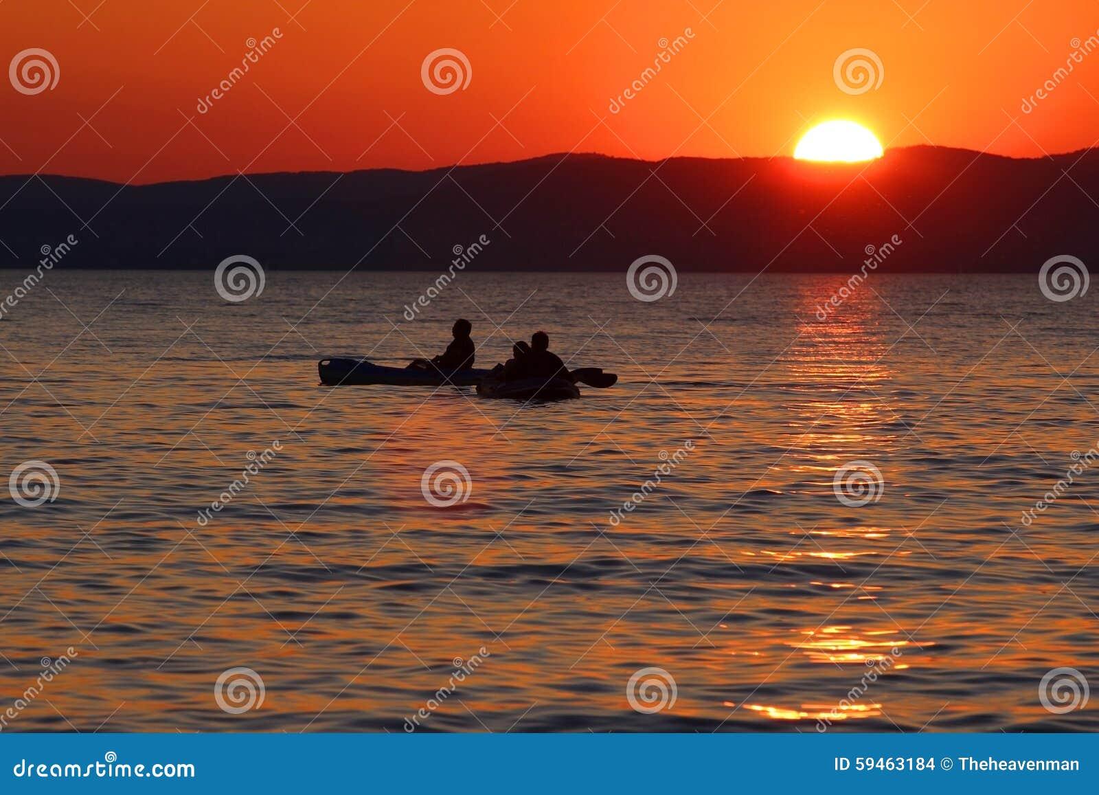 Ηλιοβασίλεμα πέρα από τη λίμνη με τις βάρκες