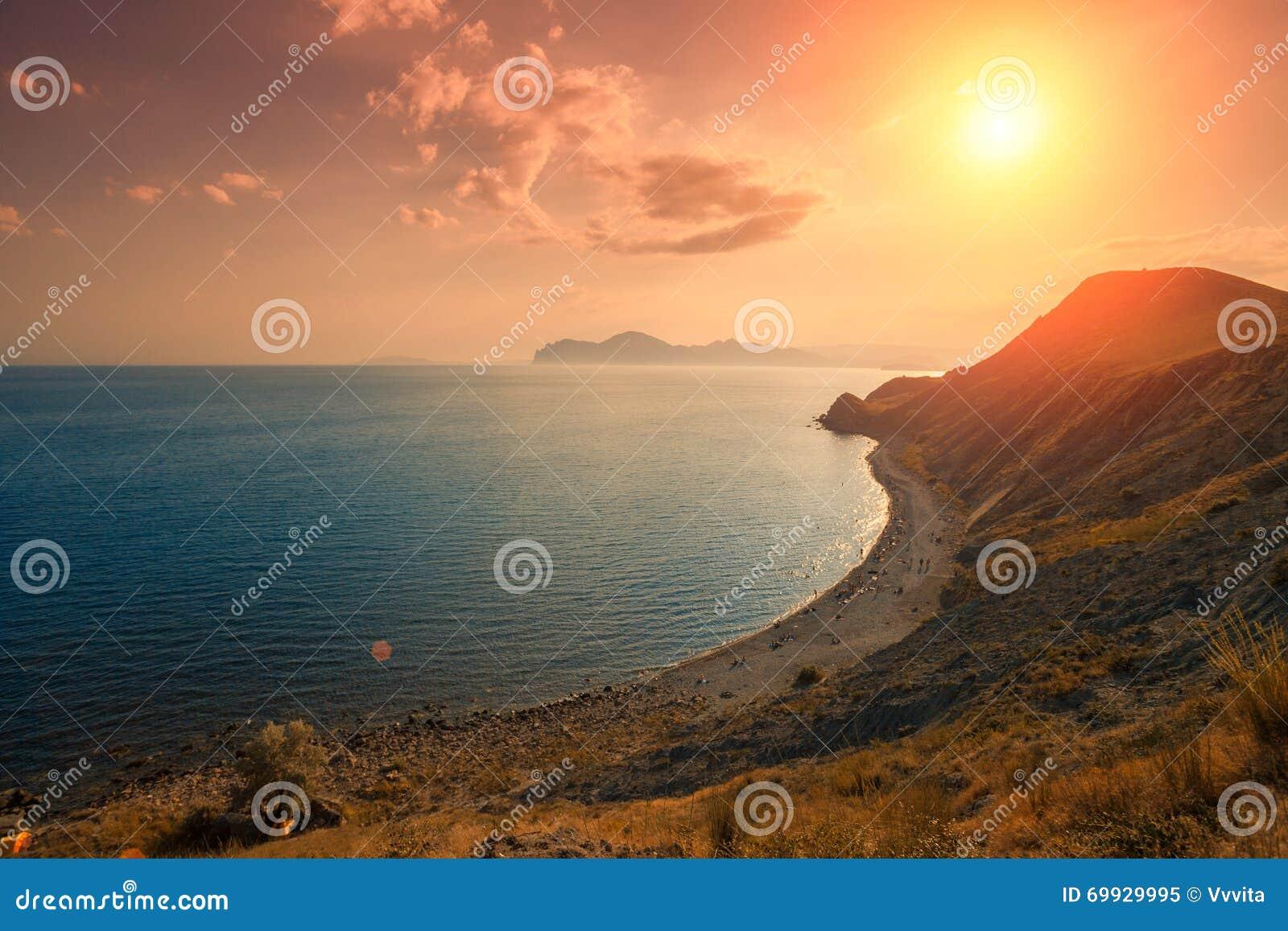 Ηλιοβασίλεμα πέρα από τη δύσκολη παραλία