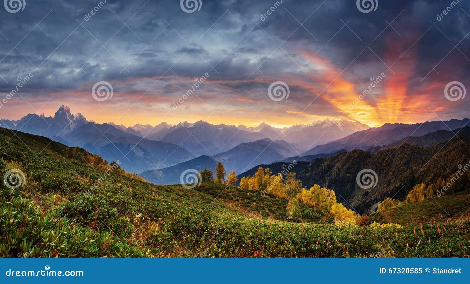 Ηλιοβασίλεμα πέρα από τις χιονοσκεπείς αιχμές βουνών