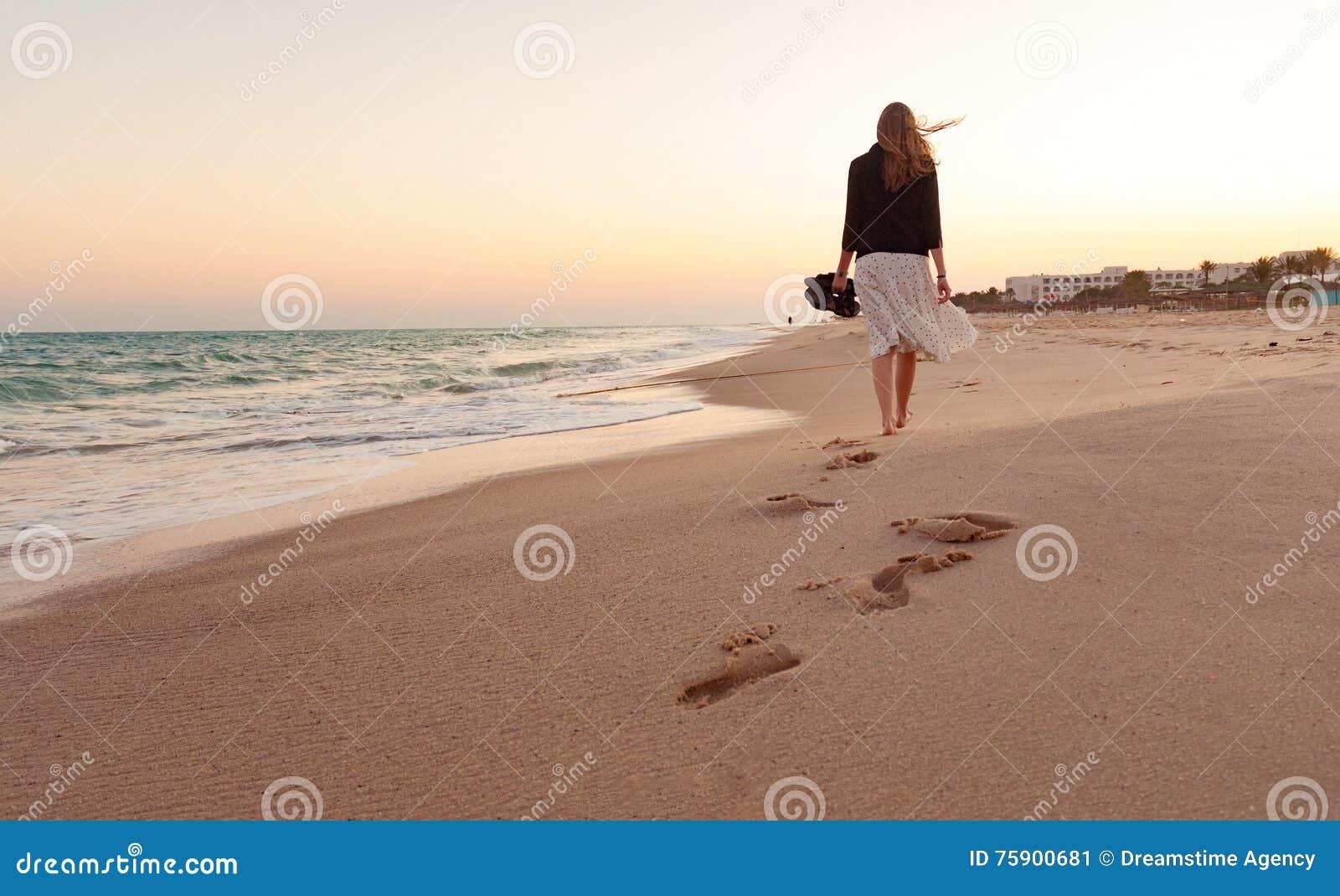 Ηλιοβασίλεμα παραλιών περπατήματος γυναικών