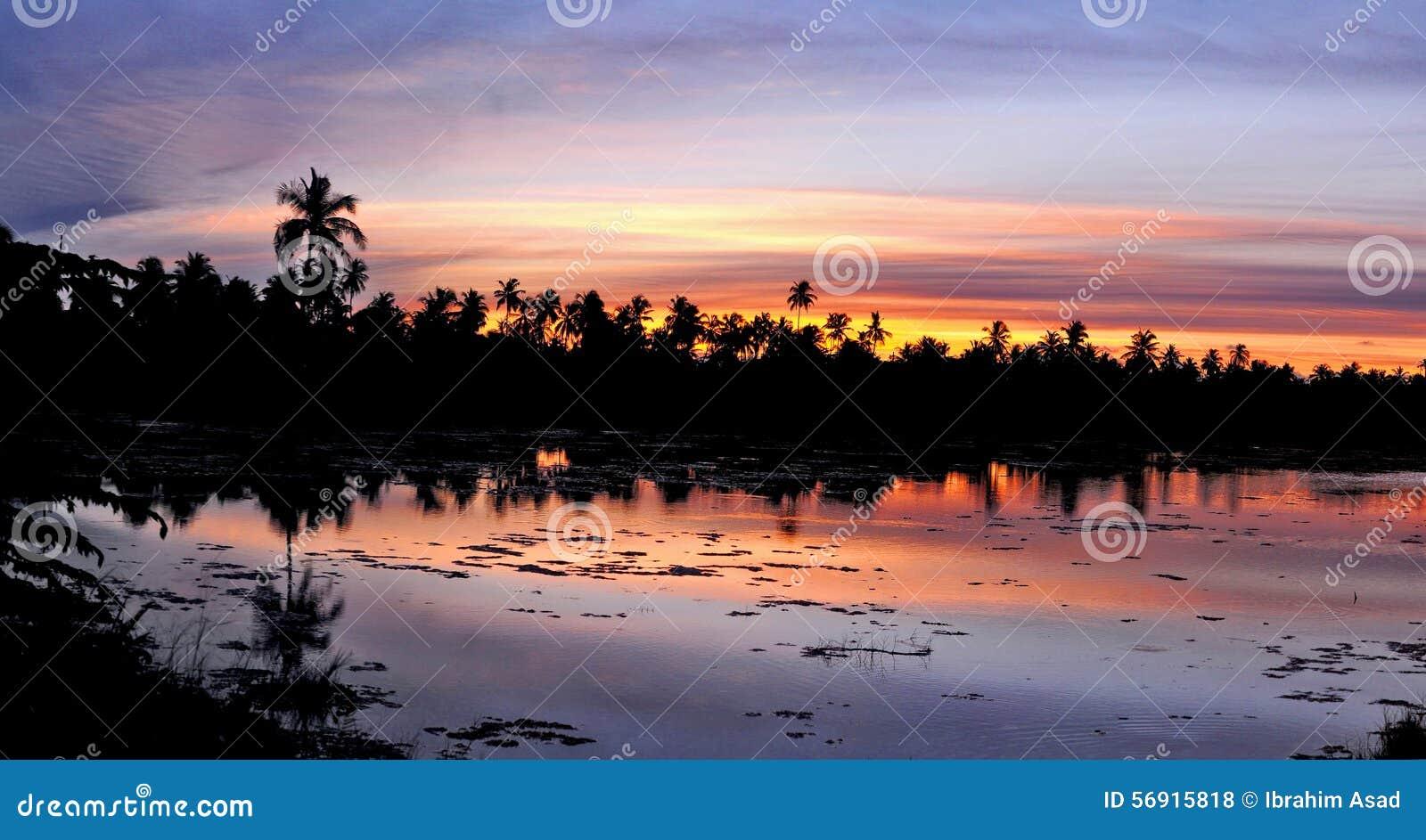 Ηλιοβασίλεμα στη λίμνη Υ γλυκού νερού Hithadhoo πόλεων Addu